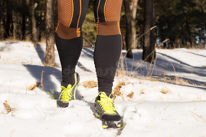 Winter trail running: man takes a run on a snowy mountain path in a pine woods. Running outdoors stock photos