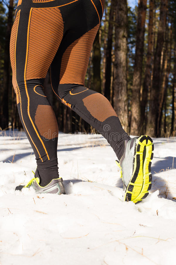 Winter trail running: man takes a run on a snowy mountain path in a pine woods. Running outdoors royalty free stock photography