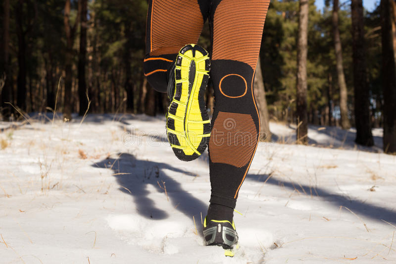 Winter trail running: man takes a run on a snowy mountain path in a pine woods. Running outdoors royalty free stock image