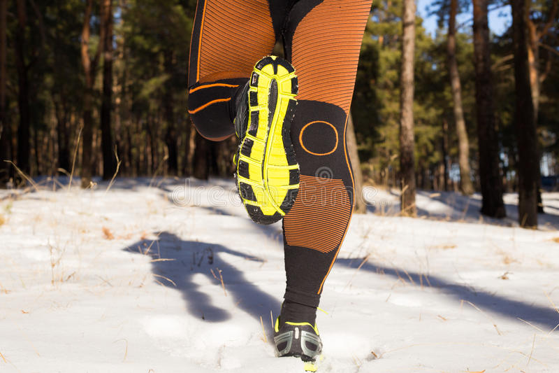 Winter trail running: man takes a run on a snowy mountain path in a pine woods. Running outdoors royalty free stock images