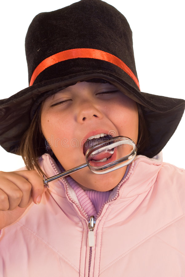 Winter Treat. A youn girl licking a beater, while wearing winter clothes royalty free stock images