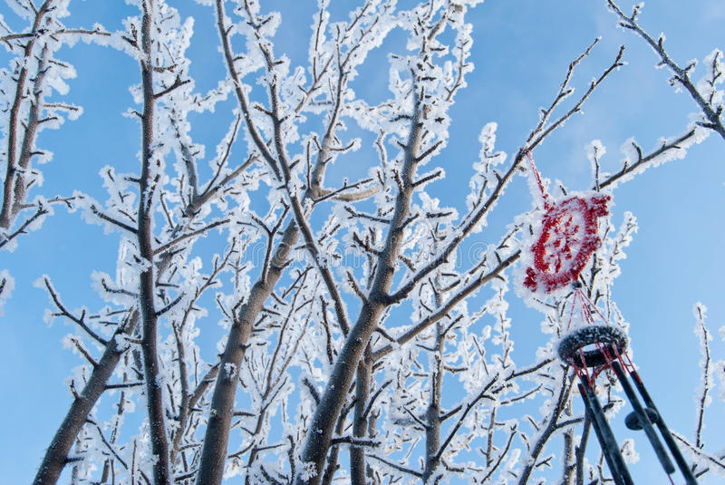 Winter tree at sky background. Frosty branches with Chinese wind chime stock photos