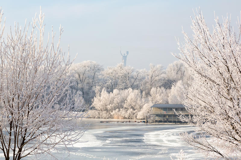 Winter trees covered with hoarfrost city river icebound. Winter town frostbitten trees covered with rime ice on the river in the distance you can see the royalty free stock images