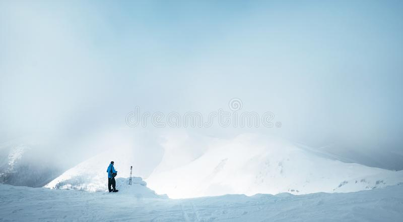 Winter Trekker staying on mountain peak he climbed and enjojing wide panorame view of valley covered by storm clouds. Active stock photography