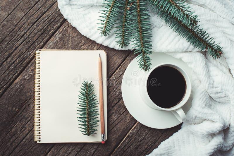 Winter- und Herbstzusammensetzung Draufsicht des Weinlesenotizbuches mit Tannenbaum und -bleistift, verziert mit Tasse Kaffee lizenzfreie stockfotos