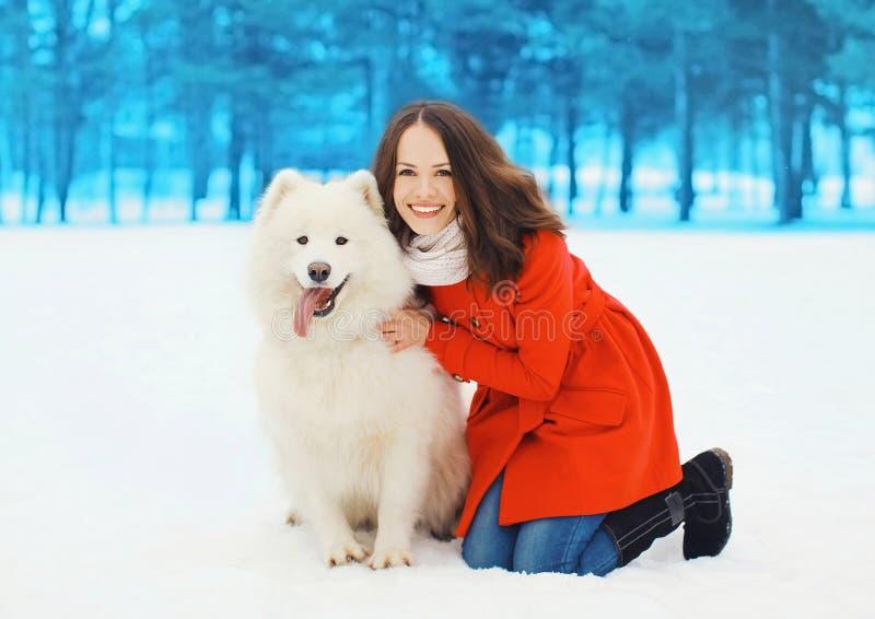 Winter und Leutekonzept - glückliche lächelnde Frau, die Spaß mit weißem Samoyedhund hat lizenzfreies stockbild
