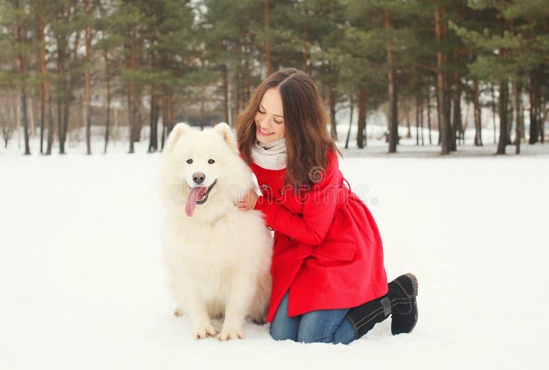 Winter und Leutekonzept - glückliche lächelnde junge Frau, die Spaß mit weißem Samoyedhund hat stockfotos