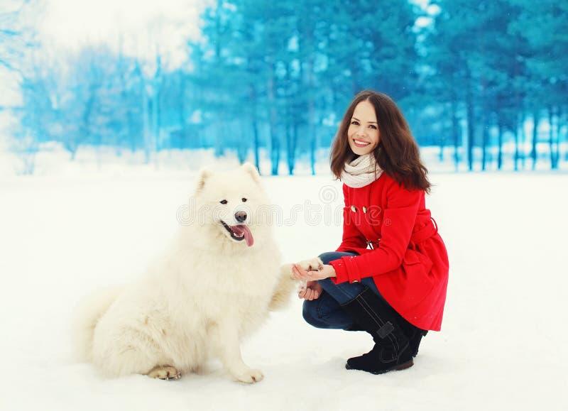 Winter und Leutekonzept - glücklicher lächelnder Eigentümer der jungen Frau, der Spaß mit weißem Samoyedhund hat lizenzfreie stockfotografie