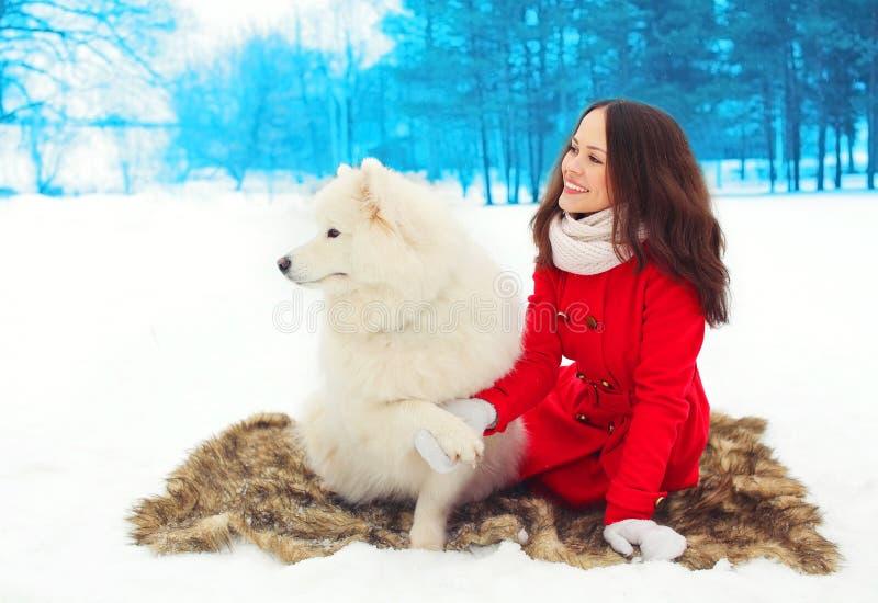 Winter und Leutekonzept - glücklicher lächelnder Eigentümer der jungen Frau mit weißem Samoyedhund lizenzfreie stockfotos