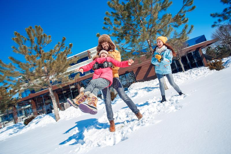 Winter vacation. Family time together outdoors man holding girl spinning laughing excited stock photography
