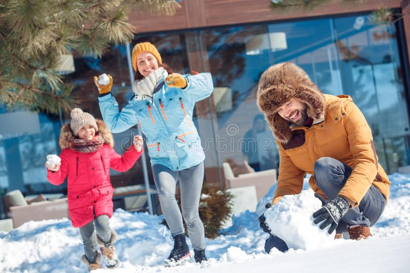 Winter vacation. Family time together outdoors man making snowball for fight while woman and girl running towards to hit stock photos