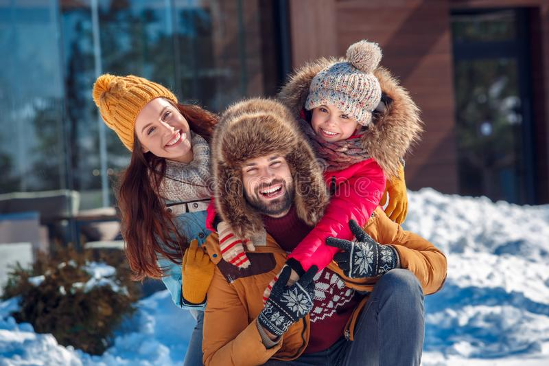 Winter vacation. Family time together outdoors sitting hugging smiling toothy close-up stock photo