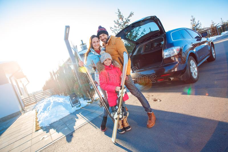 Winter vacation. Family time together outdoors standing hugging near car with skis smiling happy royalty free stock photo