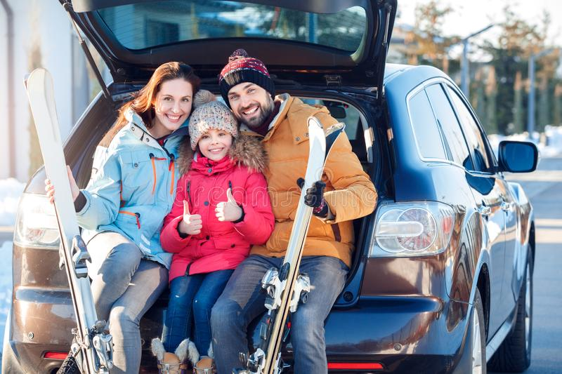 Winter vacation. Family time together outdoors standing sitting hugging at car trunk with skis smiling cheerful girl stock photos