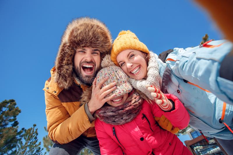 Winter vacation. Family time together outdoors taking selfie father making fun of daughter laughing cheerful bottom view stock photo