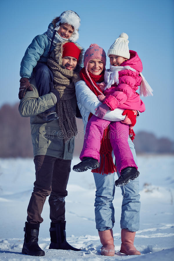 Winter vacation. Happy parents and their kids standing on snow royalty free stock photos