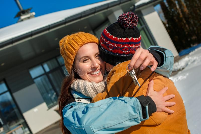 Winter vacation. Young couple standing together outdoors with keys from new apartment smiling happy royalty free stock photo