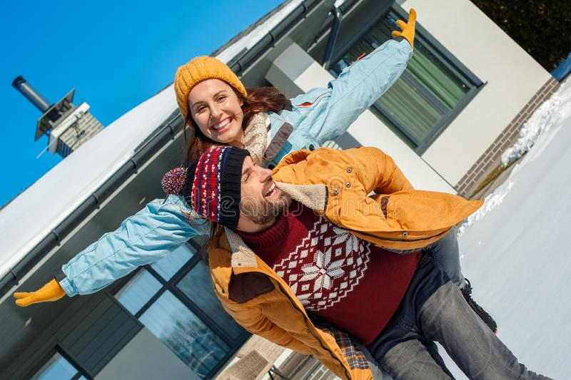 Winter vacation. Young couple standing together outdoors near house making flying pose laughing playful royalty free stock photos