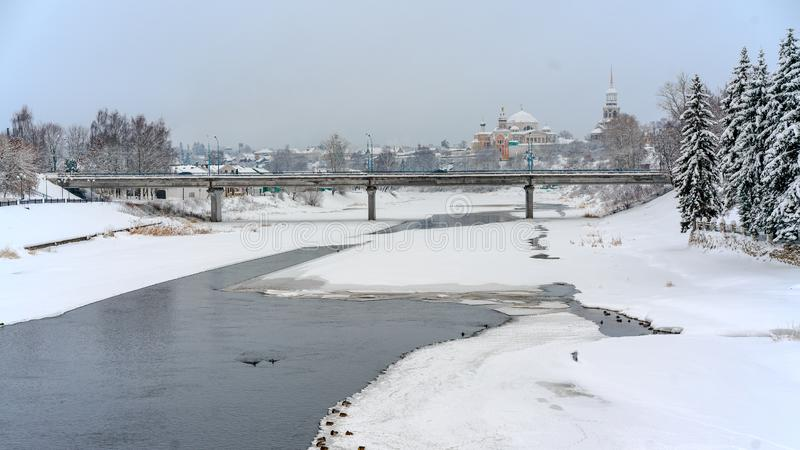 Winter view of a frozen river covered with snow, a bridge over it and an old orthodoxal monastery on the right bank royalty free stock image