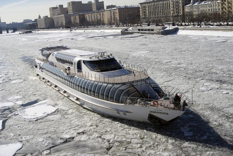 Winter view of the Moscow river embankment and cruise yacht sailing on iced water stock image