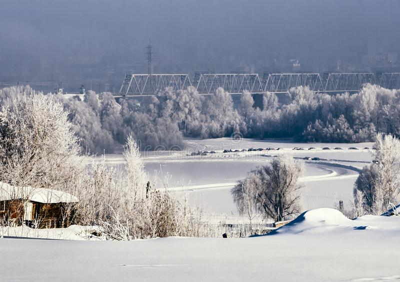 Winter view of Novosibirsk in thick fog. Winter snow-covered slope of the Ob River valley. Railroad bridge. Trees in a fluffy hoarfrost. Novosibirsk in thick fog royalty free stock image
