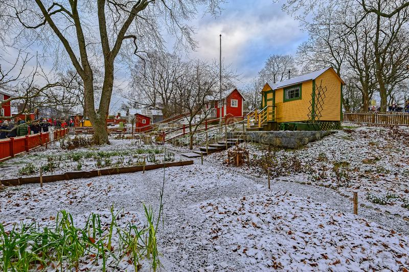 Winter view of preserved traditional colorful wooden allotments huts in Skansen the Sconce open-air Museum of Architecture and stock photography