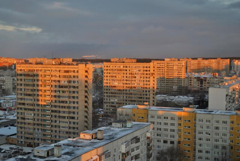 Winter view of residential district in the city of Togliatti against the backdrop of a beautiful sunset sky and clouds. Winter view of residential district in stock images