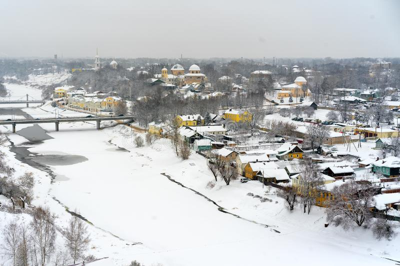 A winter view of the small old town in Russia with medieval churches, monastery, old-fashione houses. Frozen river and bridges over it royalty free stock image