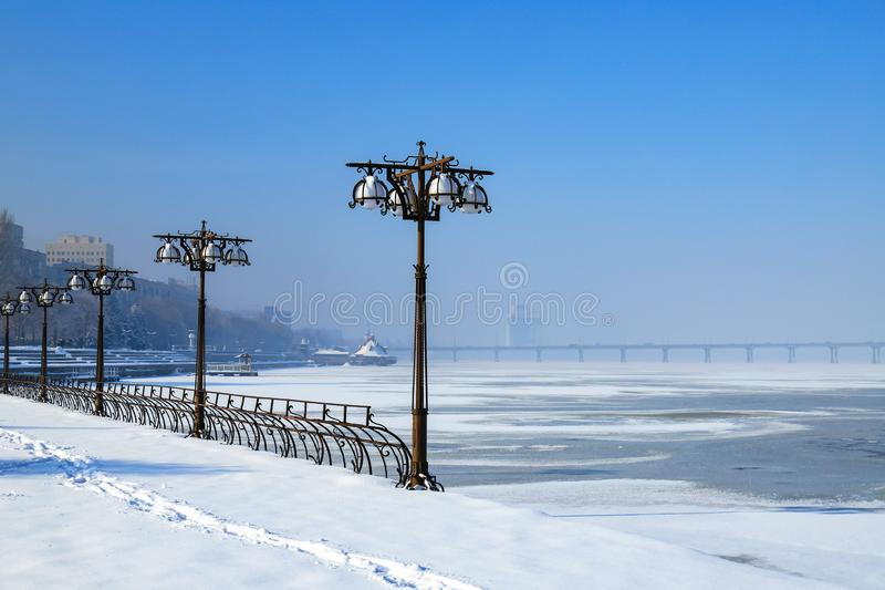 Winter view of the snow covered city on the river bank. Embankment with vintage metal lanterns and fence, Dnepropetrovsk, Dnipro. City, Ukraine stock photo