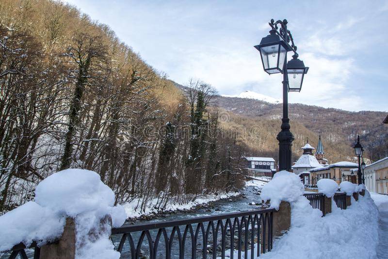 Winter view of the snow covered city on the river bank. Embankment with vintage metal lanterns. Winter view of the snow-covered city on the river bank royalty free stock photography