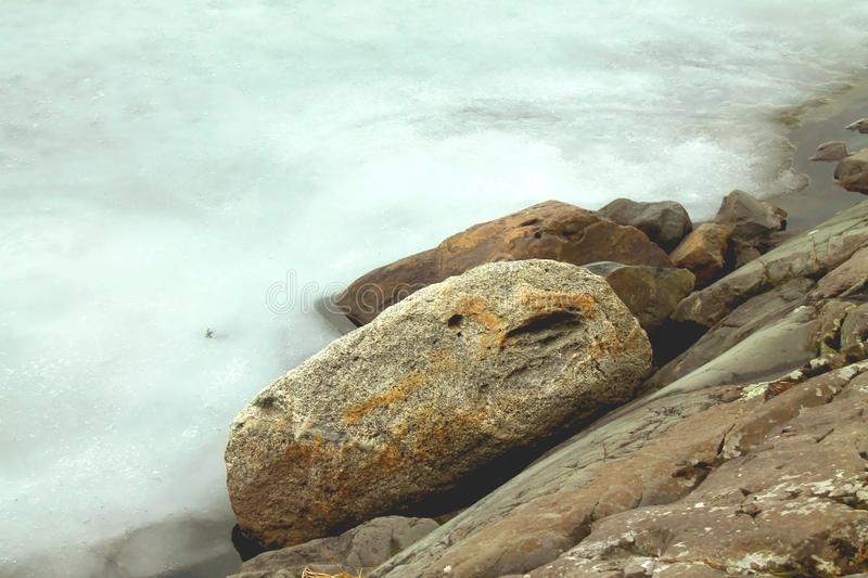 Winter view to the snowy ice and rocks on the shores of icy lake royalty free stock photography