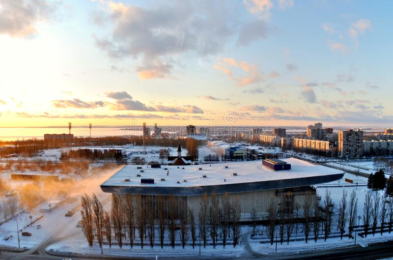 Winter view of the Volgar Sports Palace in the city of Togliatti against a stunningly beautiful sunset sky and clouds. Winter view of the Volgar Sports Palace stock image