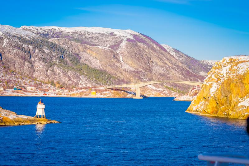 Winter views of wooden houses and stoned bridge in the coast from Hurtigruten voyage, Northern Norway. In a gorgeous sunny day and blue sky royalty free stock image