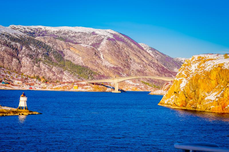 Winter views of wooden houses and stoned bridge in the coast from Hurtigruten voyage, Northern Norway. In a gorgeous sunny day and blue sky stock photos