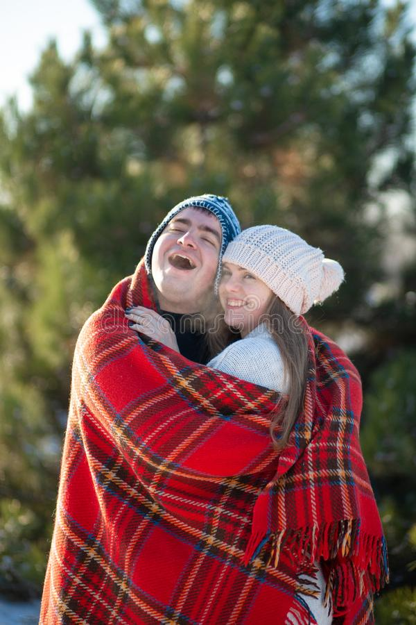 Winter walk through the woods. The guy in the red plaid blanket wraps the girl up so she gets warm.  royalty free stock images