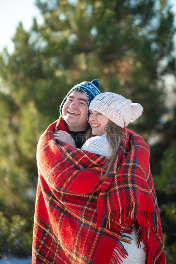 Winter walk through the woods. The guy in the red plaid blanket wraps the girl up so she gets warm.  stock photos