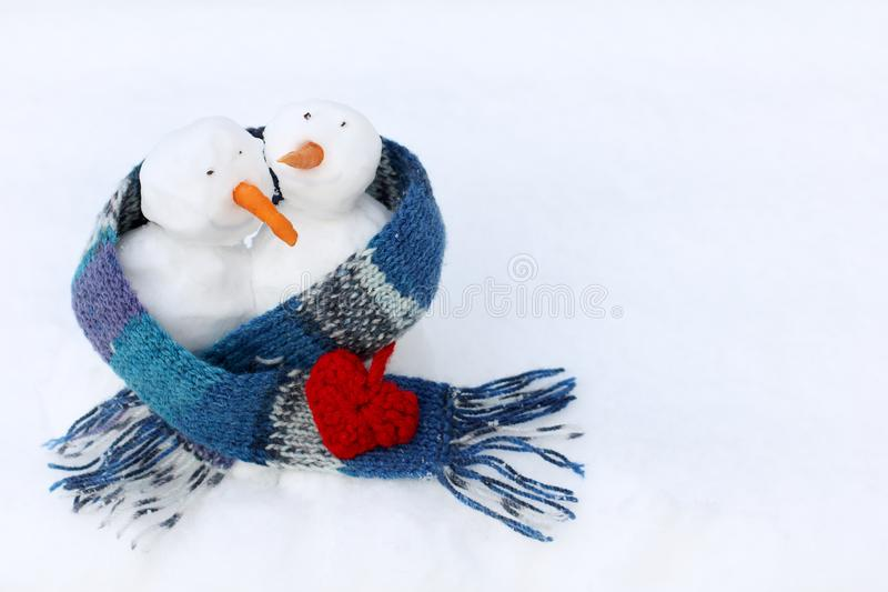 Winter walks with warm feelings. Couple of cheerful Christmas snowmans in blue scarf with knitted heart stock image