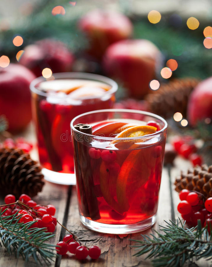Winter warm drink. Cranberry orange pomegranate punch or mulled wine, sangria wooden table. Christmas tree decorations. stock image