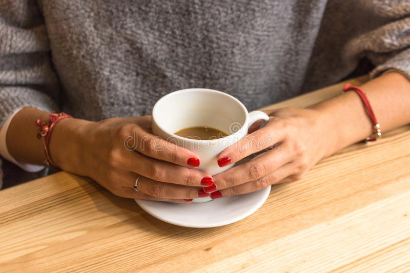 Winter warming drink. White cup of coffee in female hands. Warm your hands with a cup of hot drink. Meeting in a cafe. The girl in the coffee shop. Morning royalty free stock photography