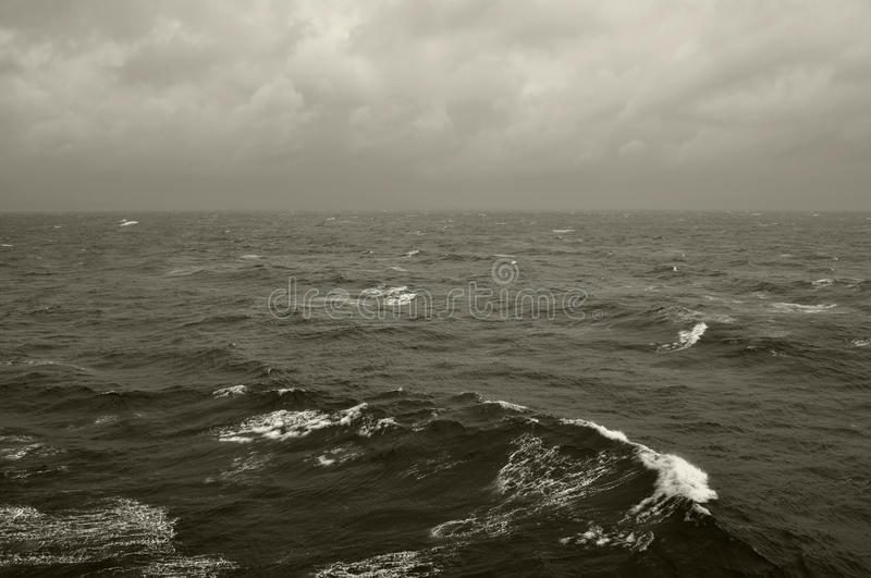 Winter waves deep sea. Winter sea waves and cloudy sky horizon. Black and white stock photography