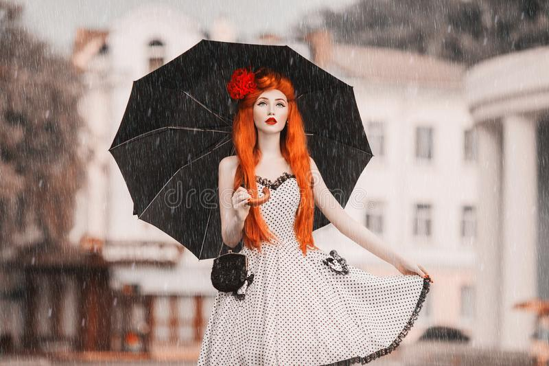 Winter weather. Autumn snow. Lonely unhappy girl in retro dress hold black umbrella. Raining in city. Wet umbrella against the stock images