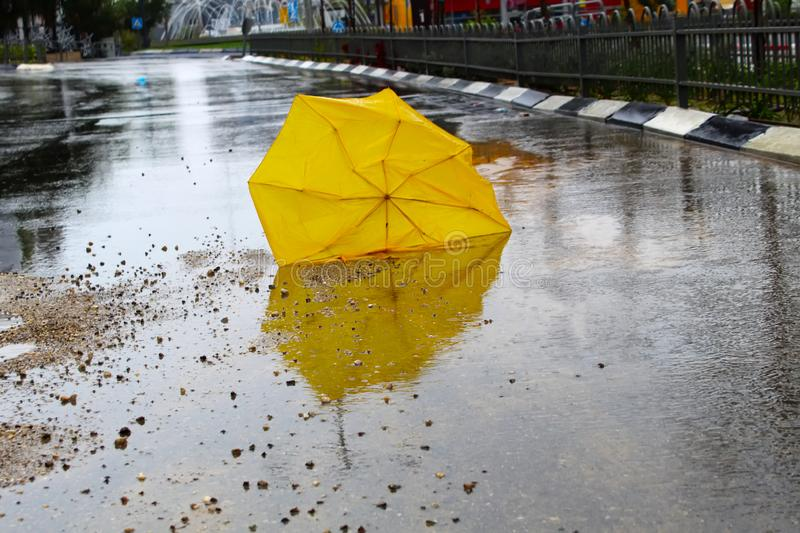 Umbrella broken by the wind with raindrops on the wet asphalt road. Winter weather, Israel. Winter weather in Israel: rain, puddles with water circles, floods royalty free stock photography