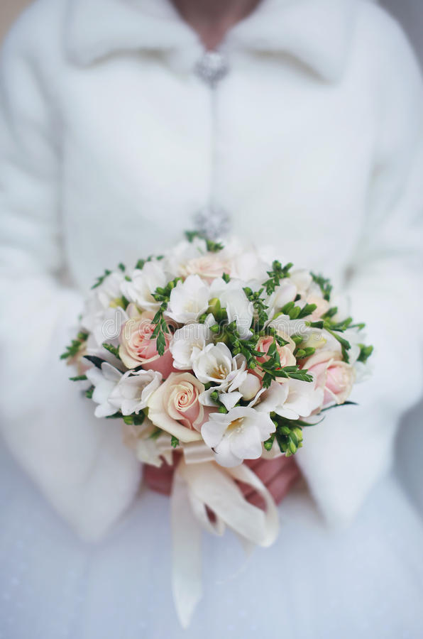 Winter wedding bouquet in hands of the bride stock photo