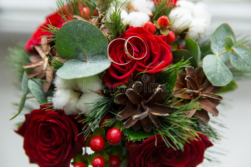 Winter wedding bouquet of red roses with wedding rings. stock photo