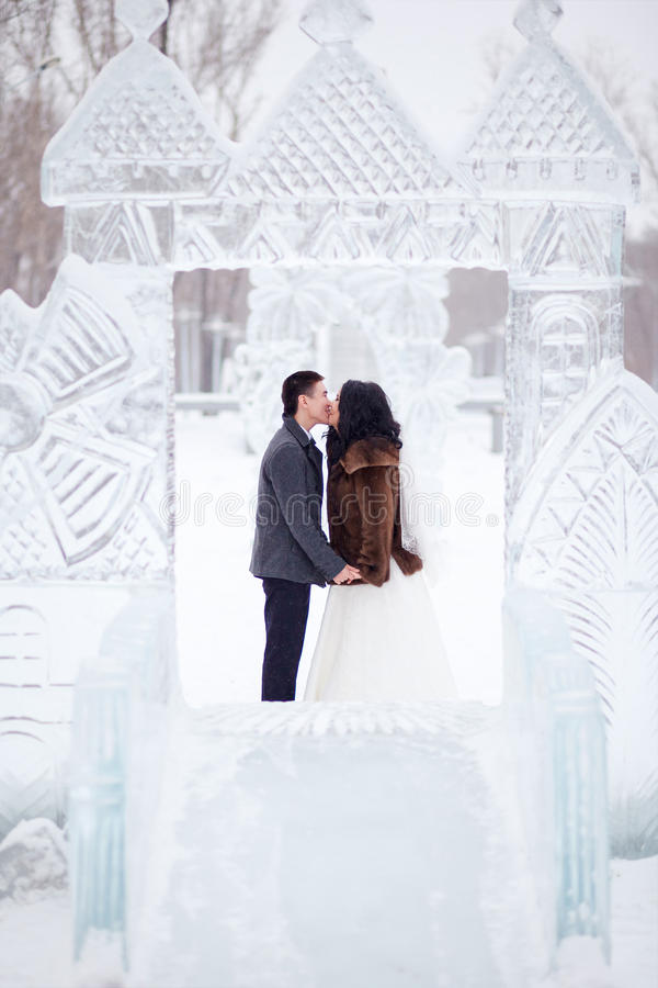 Winter wedding couple kissing in the middle of the ice figures in a snowy town, the bride in fur coat and white dress royalty free stock photography