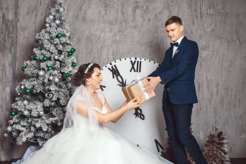Winter Wedding .Lovers bride and groom in christmas decoration . Groom holding Gift . romantic surprise for Christmas. Studio stock photos