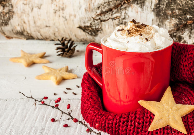 Winter whipped cream hot coffee in a red mug with cookies. Winter whipped cream hot coffee in a red mug with star shaped cookies and warm scarf - rural still royalty free stock image