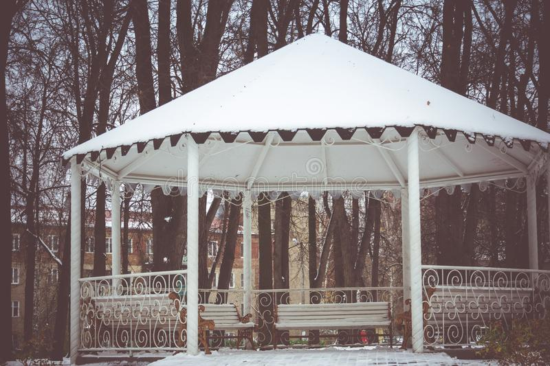Winter White Alcove. Decorative wooden alcove with benches in the city park at the winter time royalty free stock photos