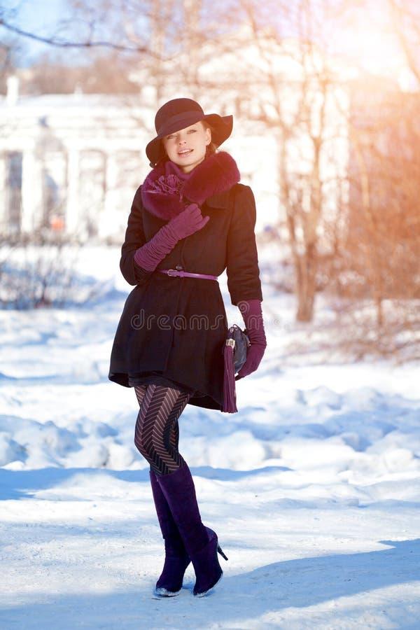 Winter woman on background of winter landscape, sun. Fashion girl in forest wonderland. Winter sunset scene. Model in sunlight, b. Acklight royalty free stock image