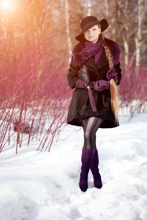 Winter woman on background of winter landscape, sun. Fashion girl in forest wonderland. Winter sunset scene. Model in sunlight, b. Acklight royalty free stock images